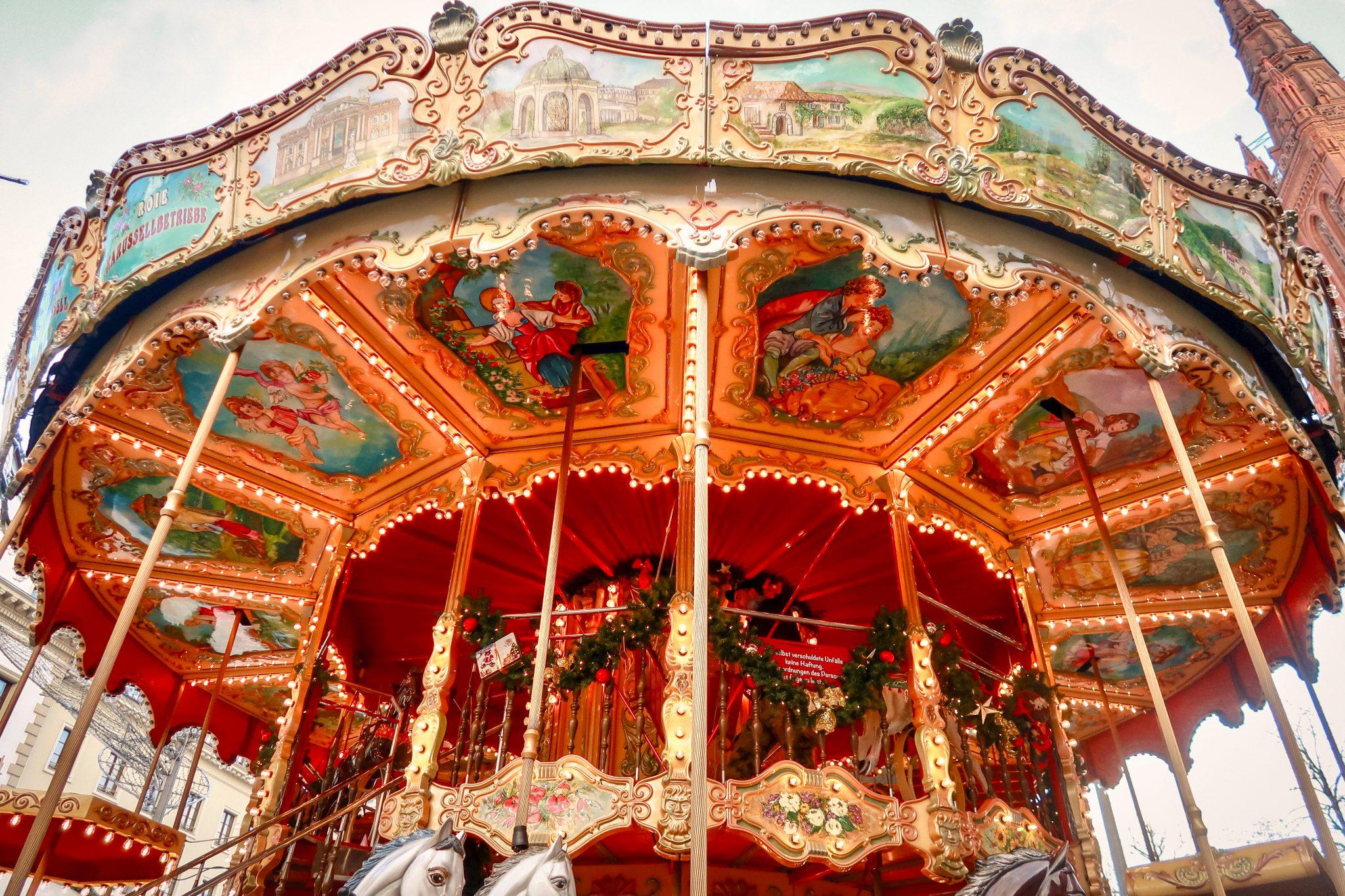 Wiesbaden, Sternschnuppenmarkt: An der Decke des historischen Pferdekarussells kannst du Motive aus Märchenbüchern erkennen.