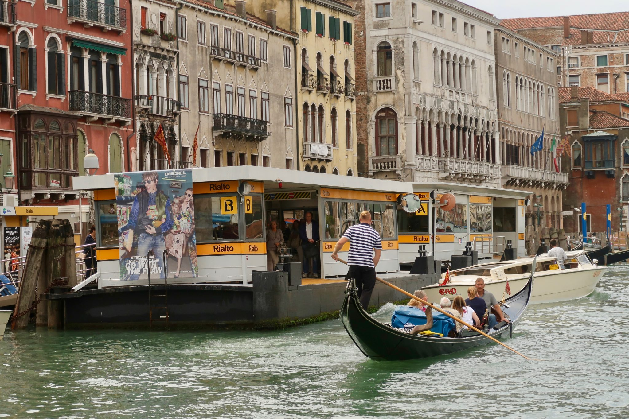 Venedig: Boothaltestelle Rialto mit einer Gondel und einem Wassertaxi