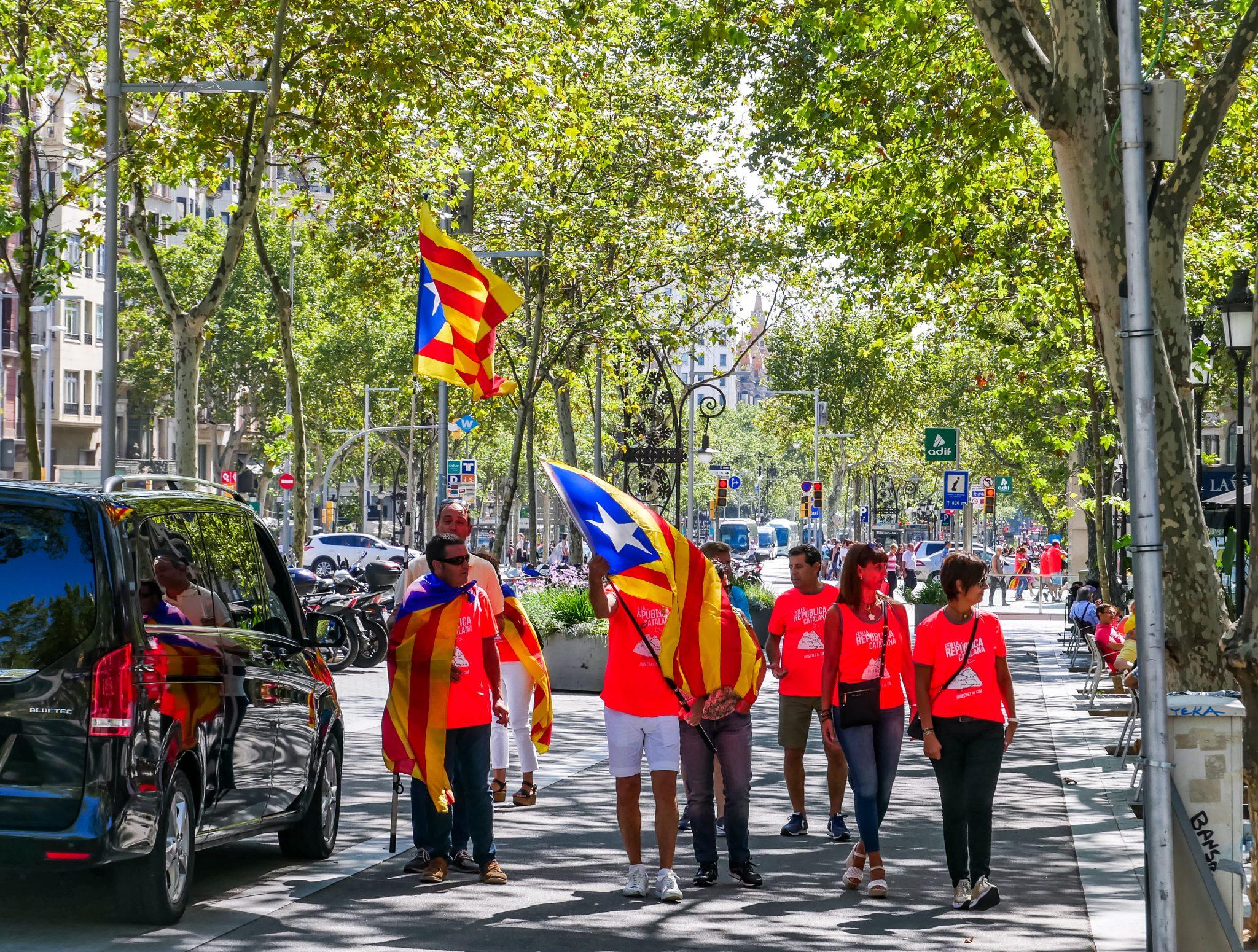 """Den ganzen Feiertag """"Diada Nacional de Cataluñya"""" über kannst du Menschen beobachten, welche die Katalanische(n) Flaggen tragen."""