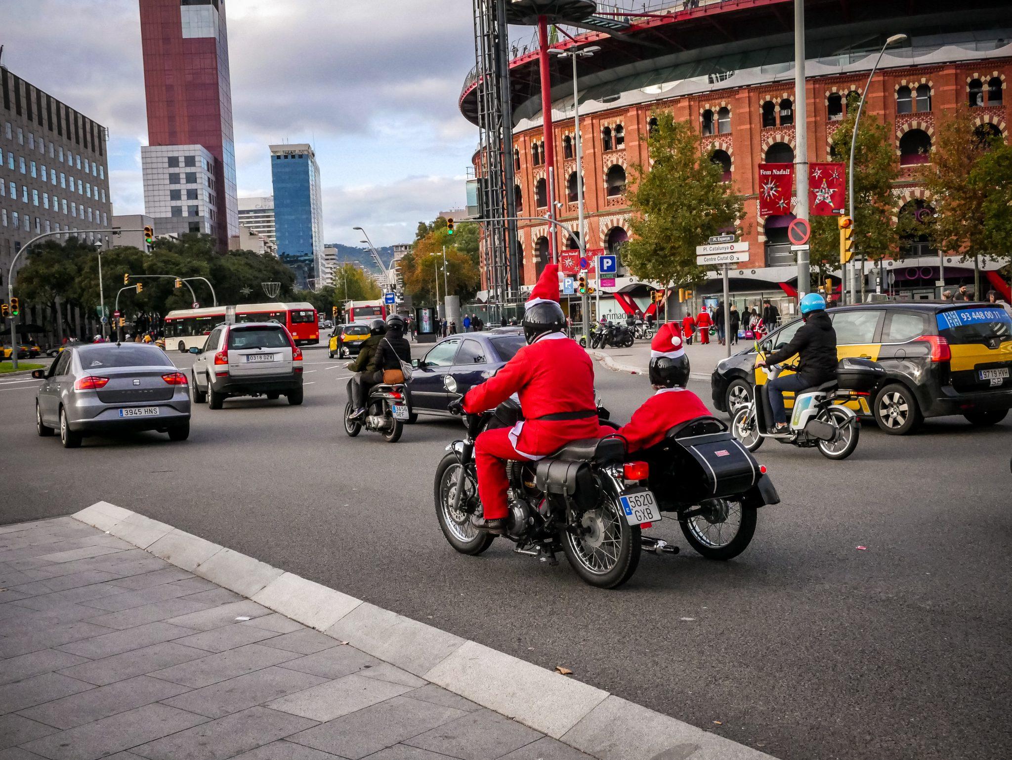 Weihnachtsmänner, welche auf ihrem Motorrad am Plaza España entlang fahren.