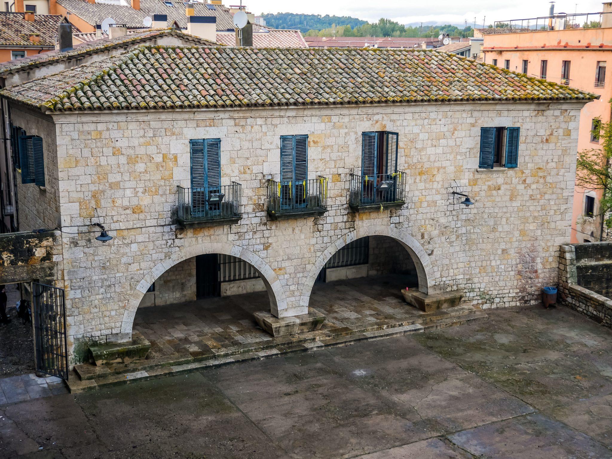 Arya Stark beobachtet in Braavos (Girona) ein Theaterspiel, welches auf einem großen Platz stattfindet.