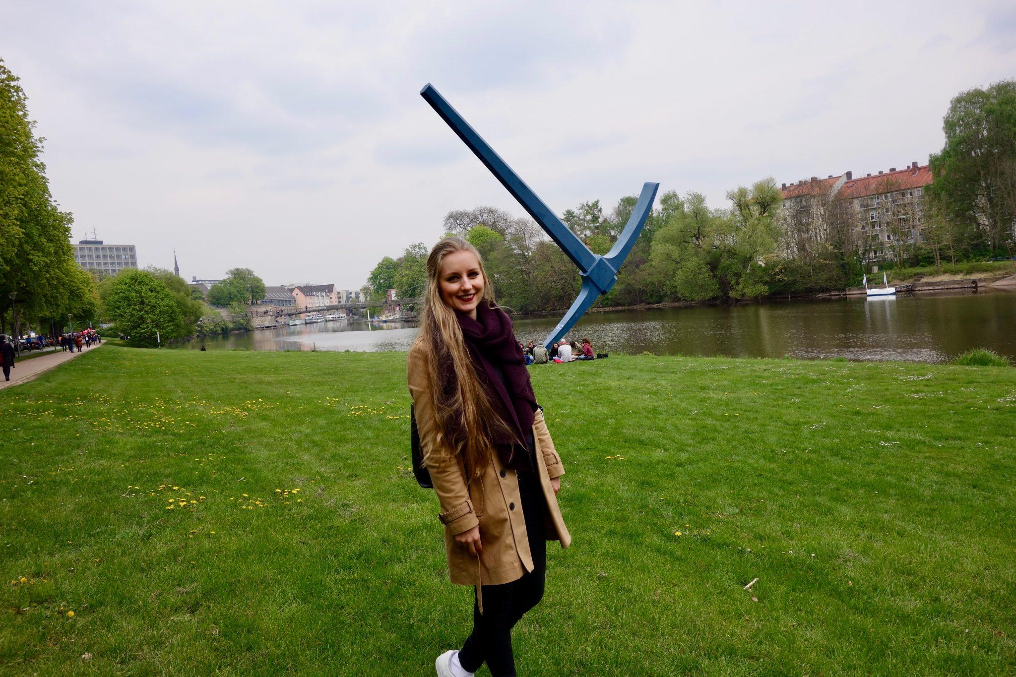 """Kassel: In der Stadt stehen überall """"Kunstwerke"""" von der Documenta (Kunstmesse), genauso wie die Spitzhacke im Hintergrund. Stell dir doch mal vor, du willst dich mit deinen Freunden verabreden und sagst: """"Hey, lass uns an der riesigen Spitzhacke am Fluss treffen."""" Hört sich schon komisch an, oder?"""